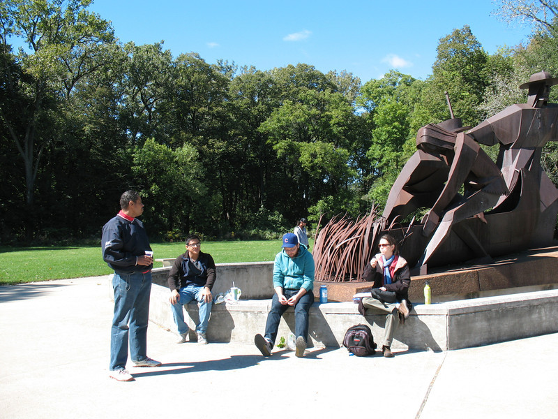 After the first leg of our day's field explorations at the Stickney Wastewater Treatment Plant of the MWRD, we convened for a picnic and a woodland hike at the Chicago Portage National Historic Site in Lyons, IL. Here we gather around the statue of Marquette and Jolliet to each lunch.<br /> L to R: Ron, Anthony, Mike Miller, and Maria